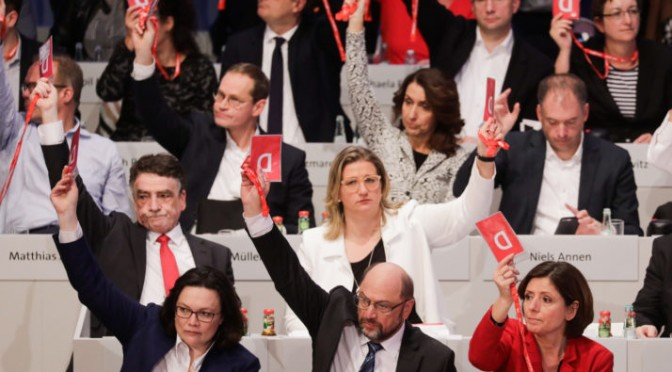 Martin Schulz (1st row, C), leader of Germany's social democratic SPD party, and leadership members hold up their voting cards during an extraordinary SPD party congress in Bonn, western Germany, on January 21, 2018. Germany's centre-left Social Democrats voted to begin formal coalition talks with German Chancellor Angela Merkel's conservatives, bringing Europe's top economy a step closer to a new government after months of deadlock. / AFP PHOTO / DPA / Kay Nietfeld / Germany OUT        (Photo credit should read KAY NIETFELD/AFP/Getty Images)